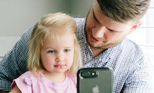 Girl and her father consulting with a physician via the smartphone app